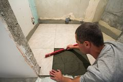 家铺磁砖改善-有平实放下砖地的杂物工 整修和建筑概念 库存照片