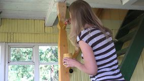 画家绘在庭院房子窗口前面的妇女女孩木楼梯专栏杆 4K 股票视频