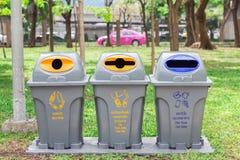 容器在玻璃瓶的公园能,塑料瓶,纸袋其他浪费的食物废物 免版税库存图片