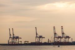 容器堆和起重机在造船厂 免版税库存图片