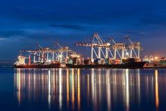 容器货物口岸有运转的起重机桥梁的货物船在s 免版税库存图片