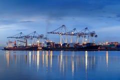 容器货物口岸有运转的起重机桥梁的货物船在s 免版税库存照片