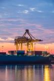 容器货物有运转的起重机桥梁的货物船在日出的造船厂 免版税库存图片