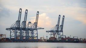 容器货物有运转的起重机桥梁的货物船在黄昏的造船厂后勤进出口的 库存图片