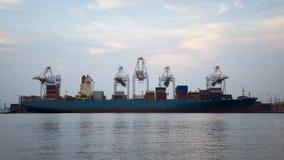 容器货物有运转的起重机桥梁的货物船在黄昏的造船厂后勤进出口的 免版税图库摄影