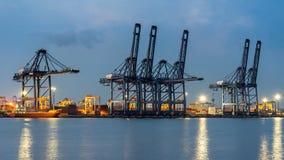 容器货物有运转的起重机桥梁的货物船在黄昏的造船厂后勤进出口背景的 库存照片