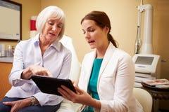 整容外科医生谈论做法与客户在办公室 库存照片