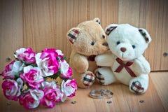 容忍在爱负担,在玫瑰色的花束和圆环附近坐 免版税库存图片
