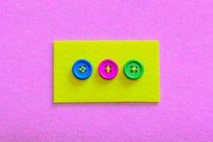 容易的方法缝合按钮到毛毡 黄色感觉与在桃红色毛毡背景隔绝的五颜六色的按钮的片断 免版税库存照片