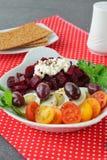 容易的早餐:甜菜根、西红柿、鸡蛋、酸奶干酪和油炸马铃薯片在一块白色板材在红色纺织品背景 库存图片