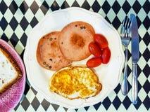 容易的美国早餐包括煮熟的煎蛋、胡椒猪肉香肠、红色蕃茄和烤整个五谷 免版税库存照片