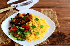 容易的菜炒饭、茄子用西红柿酱,新鲜的蕃茄和黄瓜沙拉在一把白色板材、叉子和刀子 图库摄影
