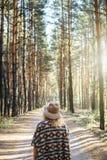 宽充满的呢帽的妇女和在一条土路的地道雨披身分在有雾的松树森林垂直的取向 库存照片