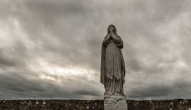 宽容圣母玛丽亚雕象灰色天空 库存照片