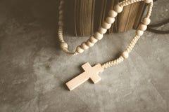 宽容念珠成串珠状与在水泥桌祷告的旧书,罗莎 免版税库存图片