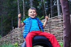宽广的微笑的小男孩坐轮胎摇摆 免版税库存照片