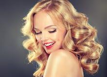 年轻宽微笑的白肤金发的头发的女孩模型 免版税库存照片