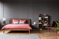 宽敞卧室内部的真正的照片与桃红色床身分的 库存照片