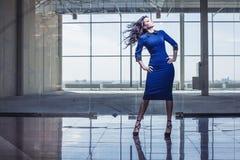 宽敞大厅的美丽的妇女与飞行头发 图库摄影