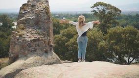 宽松衣裳的逗人喜爱的苗条年轻女人沿她的口袋慢慢地上升渐近峭壁和到壮观 影视素材