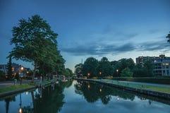 宽沿途有树的运河夜视图,大厦和灯张贴照明设备在黎明在韦斯普 库存图片