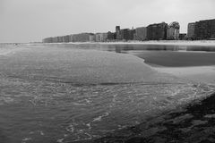 宽海滩有风暴的北海在多云冬日挥动 沿黑白的海岸的大厦 图库摄影