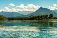 宽蓝色河在山流动在一个夏日 免版税库存照片