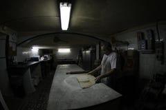 宽贝克在古色古香的面包店工厂和商店的工作 免版税库存照片