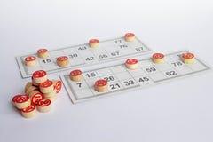 宾果游戏或乐透纸牌比赛 木小桶在卡片的乐透纸牌 卡片和芯片演奏的宾果游戏在一张白色桌上 免版税图库摄影