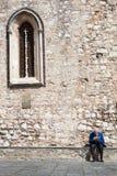 寂寞退休的年长人读书报纸 古老墙壁和窗口 免版税库存照片