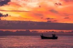 寂寞:一条小船在观看在火的一个新早晨特别天空在黎明 免版税库存照片