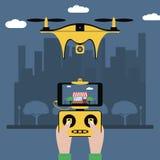 寄生虫和遥控 手拿着与屏幕的一个无线电控制器对飞行在城市的quadcopter 与照相机的Quadricopter 图库摄影