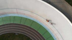 寄生虫在室内自行车赛场附近飞行在基辅 在自行车赛车道的专业循环的队训练 轨道自行车ridi的年轻嬉戏人 影视素材