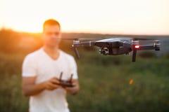 寄生虫在有遥远的控制器的人前面盘旋在他的手上 Quadcopter在飞行员附近飞行 拍空中照片的人 图库摄影