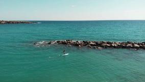 寄生虫在美丽的岩石海滨附近飞行 年轻嬉戏人鸟瞰图一口的 漂浮沿岩石石头的可爱的男孩 O 股票录像
