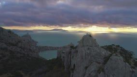 寄生虫是在站立在岩石顶部的登山人人的快速的落后飞行在日出 鸟瞰图