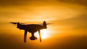 寄生虫有数字照相机的方形字体直升机在准备好的日落飞行为 免版税库存图片