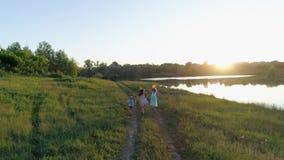 寄生虫视图、快乐的孩子有色的丝带的和球在手上在绿色草甸跑 股票录像