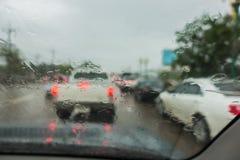 密集的交通在与雨珠的一个雨天在汽车玻璃 库存照片