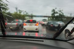 密集的交通在与雨珠的一个雨天在汽车玻璃 免版税图库摄影