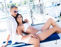 富人和一名美丽的妇女泳装的在小船 免版税库存图片