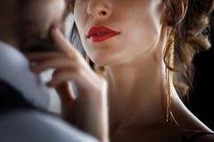 富人诱惑红色晚礼服的妇女 免版税库存照片