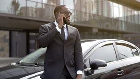 富人谈话在有微笑的电话在面孔,愉快的新郎在婚礼之日 库存照片