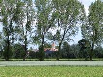 富兰德:与教会的领域背景通过被看见的树的 库存图片