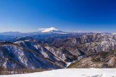 富士山和多雪的山 免版税库存图片