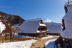 富士山在一个清楚的冬日,在传统日本盖的房子之间在Iyashino佐藤Nenba传统村庄的 免版税库存照片