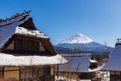 富士山在一个清楚的冬日,在传统日本盖的房子在Iyashino佐藤Nenba传统村庄的 库存图片