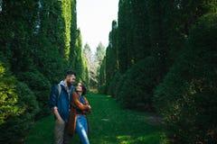 富感情地拥抱丈夫的妻子,当站立在庭院里时 库存图片