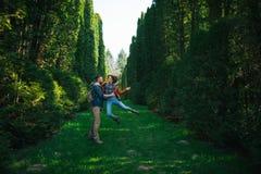 富感情地拥抱丈夫的妻子,当站立在庭院里时 免版税库存图片