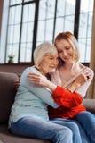 富感情地拥抱年长夫人的迷人的妇女坐长沙发 免版税库存照片